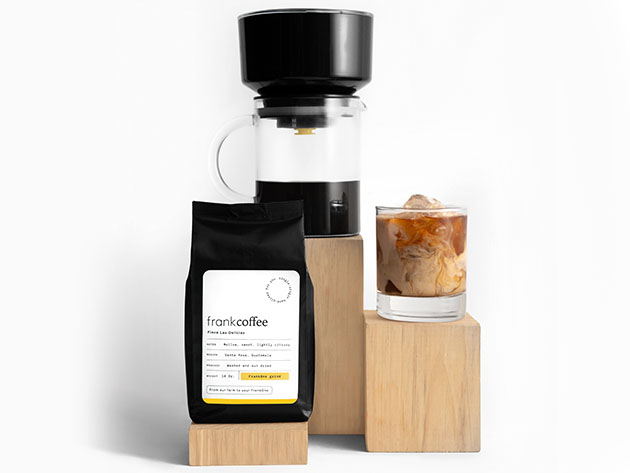 A coffee brewing set, featuring a bag of coffee, brewing device, and cup