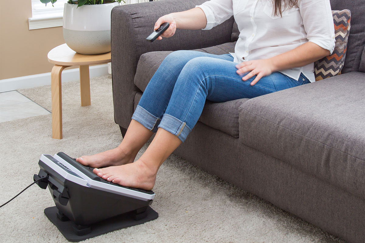 A person sitting on a couch using a foot massager