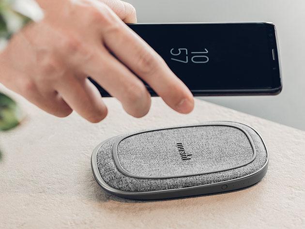 A person holding a phone near an external battery