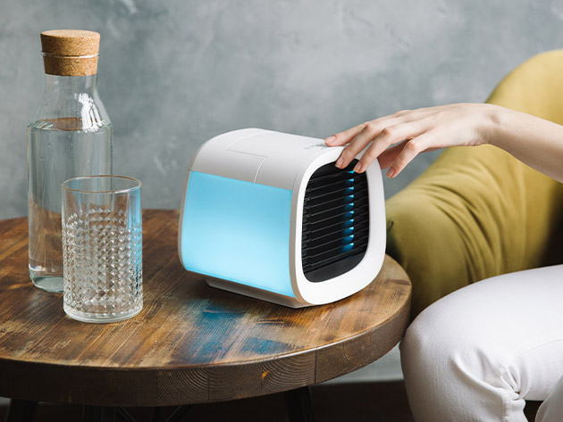 The EvaChill EV-500 Personal Air Conditioner on a table next to some water.