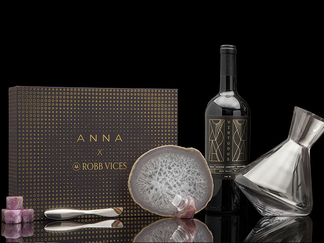 "A box that reads ""ANNA X ROBB VICES,"" next to a bottle of wine, decorative stone, and crystal decanter"