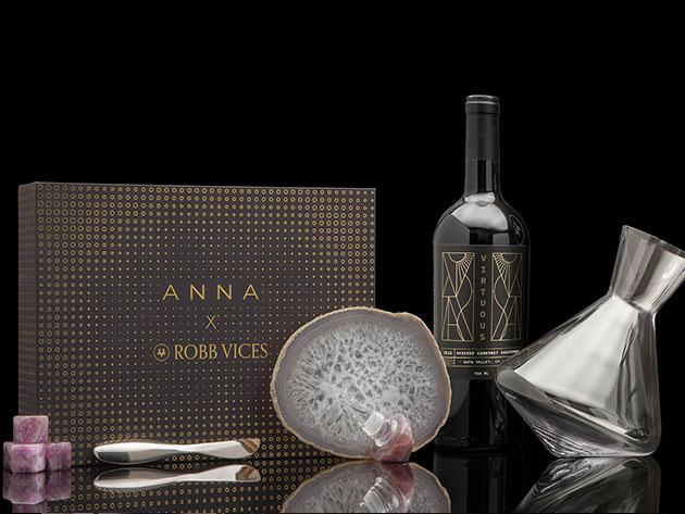 """Una caja que dice """"ANNA X ROBB VICES,"""" junto a una botella de vino, piedra decorativa y jarra de cristal"""