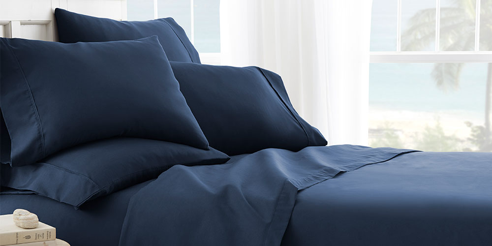 A bed with navy sheets