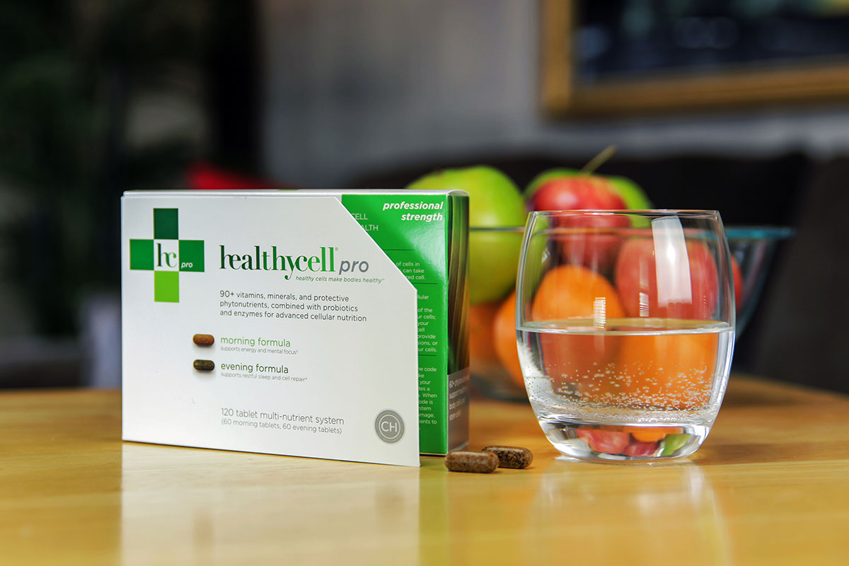 A box of healthycell pro supplements, on a table with a glass of water