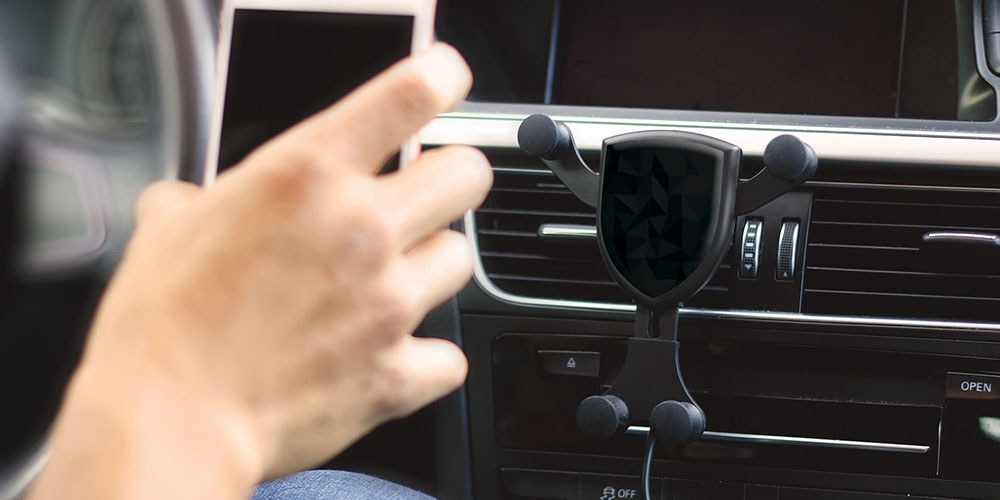 A wireless phone charger for cars, with a person holding their phone