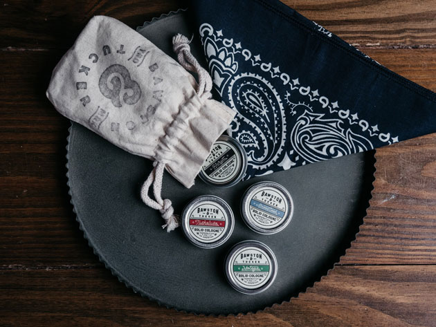 A black circular tray, with a black bandana, four containers of solid perfume, and a pull string bag
