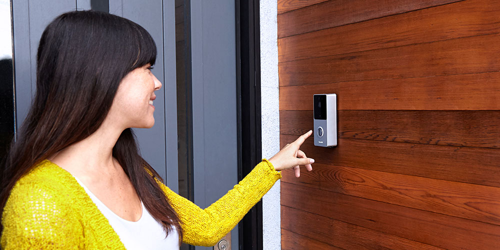 A woman uses a RemoBell doorbell