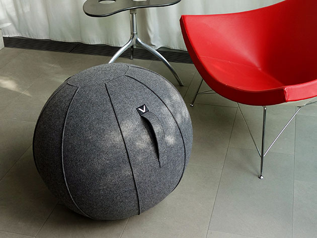 A grey felt ball chair, next to a red chair and a small table