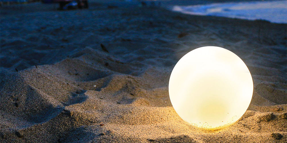 A glowing circular lamp on the beach