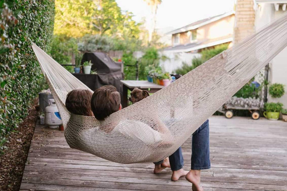 Two people sitting in a hammock