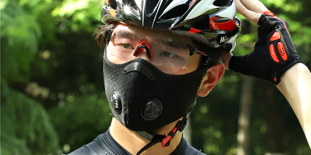 A person wearing a face mask and a bike helmet