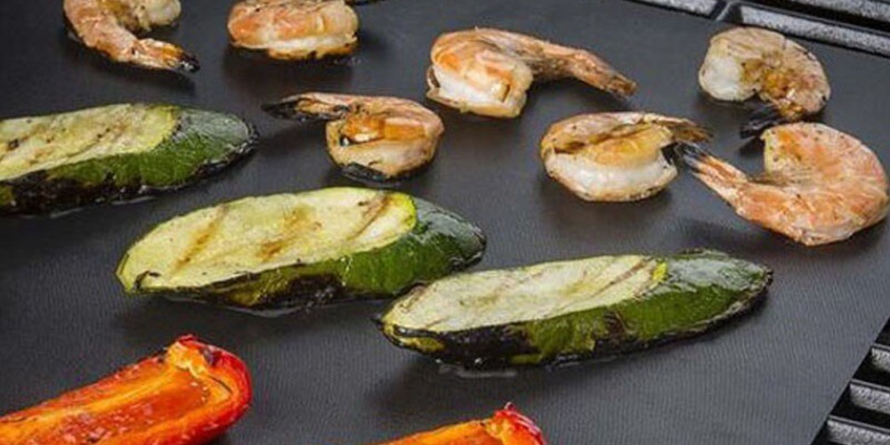 A grilling pad with shrimp, zucchini and red pepper.